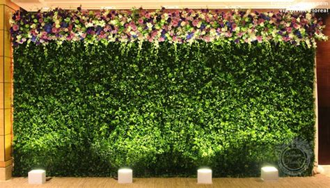 A Greenery Wall With Floral Accents Modern Wedding