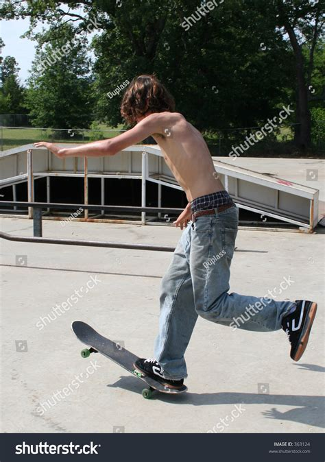 boy shirtless skateboarding outdoor stock photo