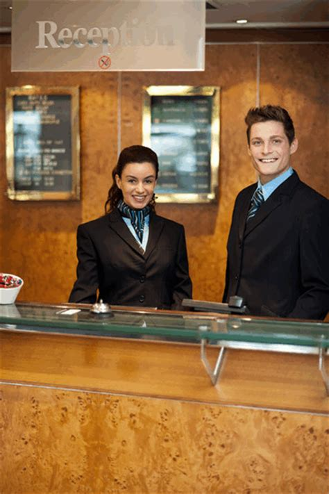 hilton employee help desk hotel lobby staff wearing black suits with torquoise blue