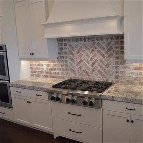 red brick herringbone cooktop backsplash transitional