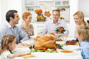 family at the dinner table at the thanksgiving day health newswire