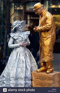 Gold man with Silver lady street performer chatting at ...
