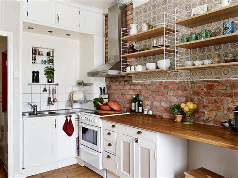 mała biała kuchnia z drewnianym blatem i ścianą zdjęcie