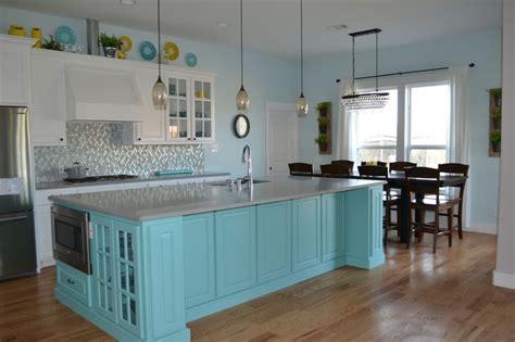White kitchen cabinets with teal island, grey quartz
