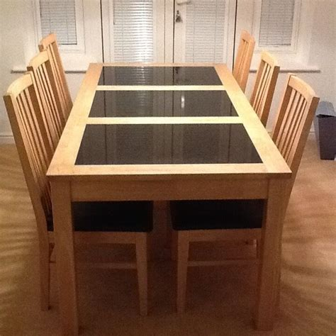 blonde wooden dining table  black inlaid marble panels