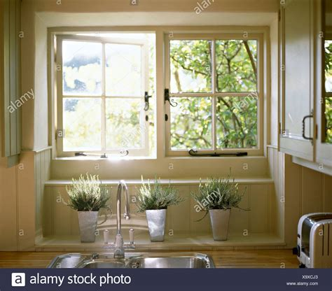 window above kitchen sink white in steel pots below open casement window