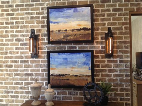 brick wall with sconces and pictures