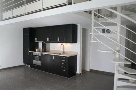 cuisine ouverte meuble noir et plan de travail blanc