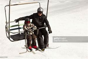 A Father And Son On A Chair Lift At A Ski Area Photo