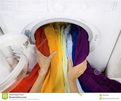 Woman Taking Color Laundry From Washing Machine Stock