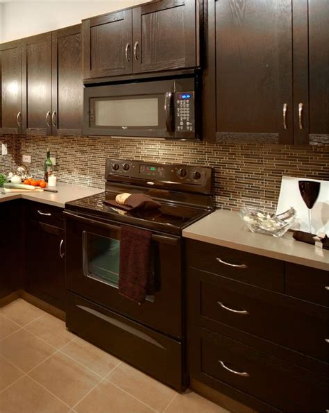 dark kitchen cabinets with light countertops modern kitchen with glass mosaic backsplash taupe floor