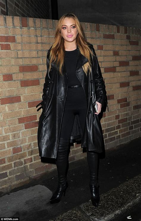 Lindsay Lohan in a black leather outfit as she puts on a playful display leaving Sexy Fish ...