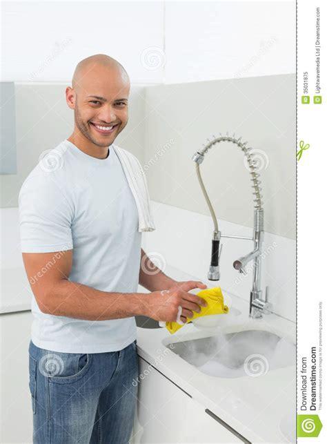 homme de sourire faisant la vaisselle 224 l 233 vier de cuisine photo libre de droits image