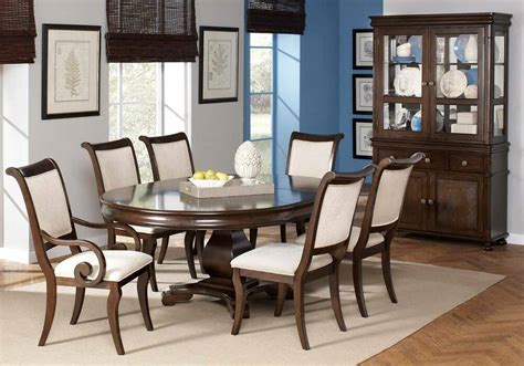 oval dining table beige scroll arm chairs