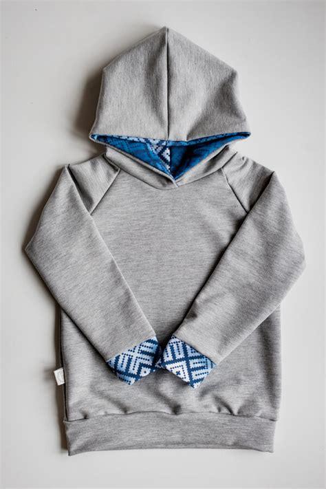 Džemperis gaiši pelēkā krāsā ar zilo rakstu kapuci ...