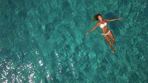 Aerial - Beautiful young woman floating on water surface ...