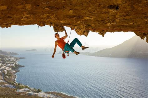 Male Rock Climber Climbing Along Roof Cave Stock