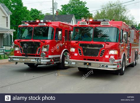 Two Red Fire Trucks Rushing To The Scene Of A Fire On A