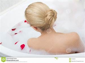 Back View Of Woman Relaxing In Bath With Red Flower Petals
