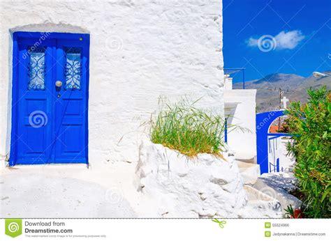 blue wooden door white wall  flowers  greece stock