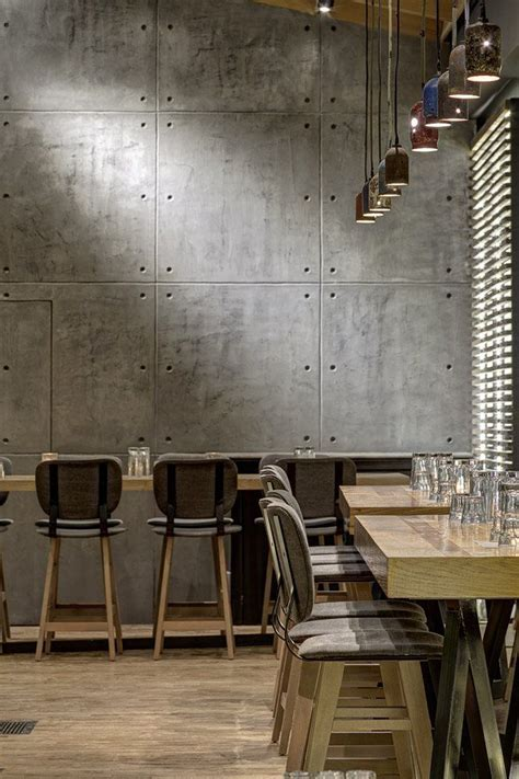 bar height tables, pendant lights, concrete wall