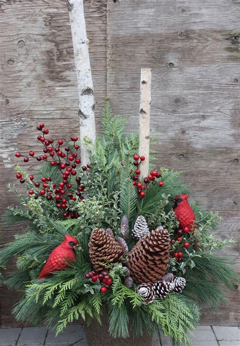 winter urn arrangement  pinecones red berries