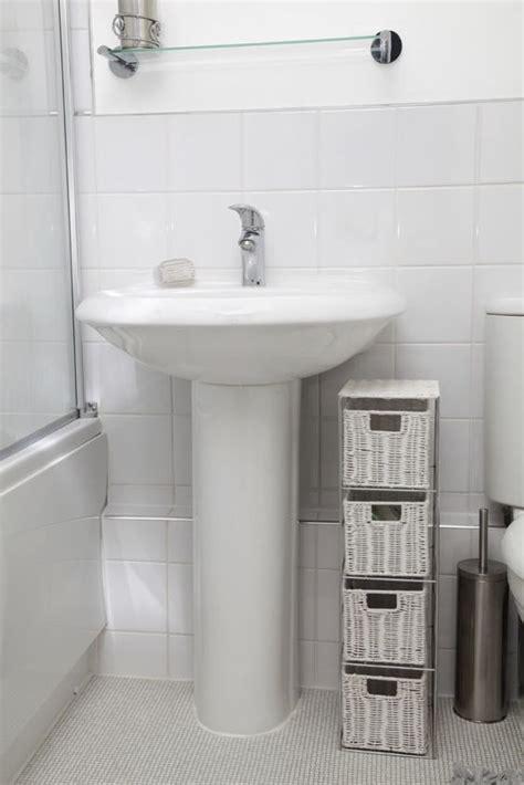 white pedestal sink  nearby wicker storage http