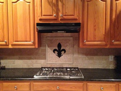 Travertine backsplash. Fleur de lis matches granite