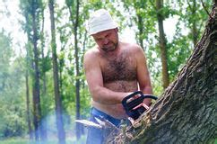 fit carrying a chainsaw in woodland stock photo
