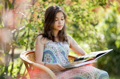Girl Reading Book Sitting In Wicker Chair Outdoor In Summer Day  Stock Photo Colourbox