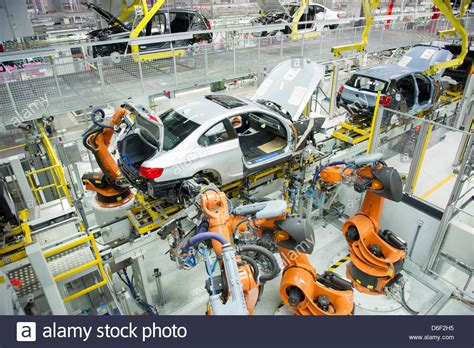Several robots work on a car at a factory of car ...