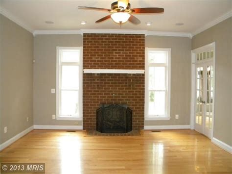 brick fireplace light wood flooring taupe gray walls