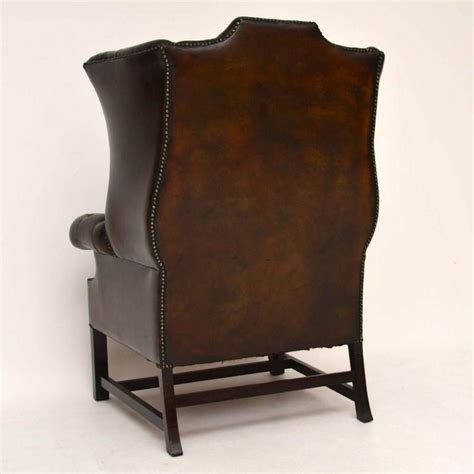 pair of carved and upholstered mahogany wing antique buttoned leather wing back armchair at 1stdibs