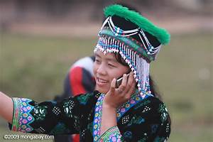 Hmong girl in traditional apparel talking on a mobile ...