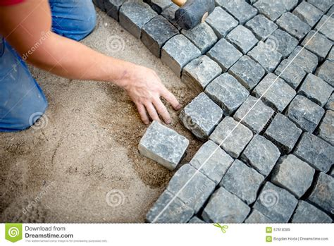 construction worker laying cobblestones  stone blocks