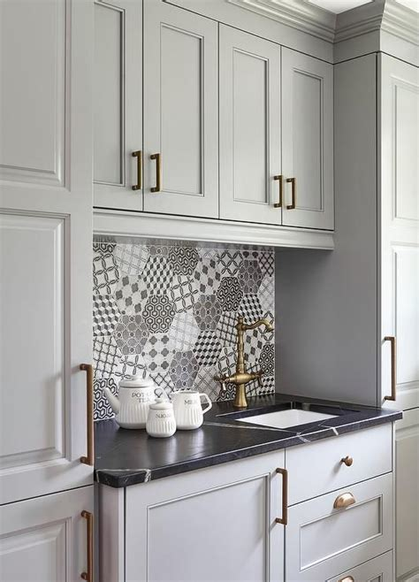 Gray kitchen pantry cabinets accented with brushed brass