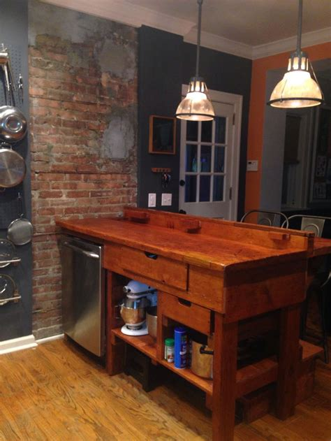 Kitchen Island Ideas - antique workbench as kitchen island with exposed brick chimney retrofitted for dishwasher