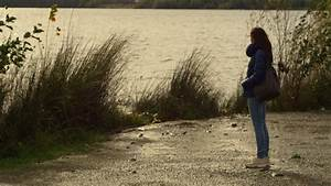 Young Woman Standing Alone And Sad Near A Lake In A Cold ...