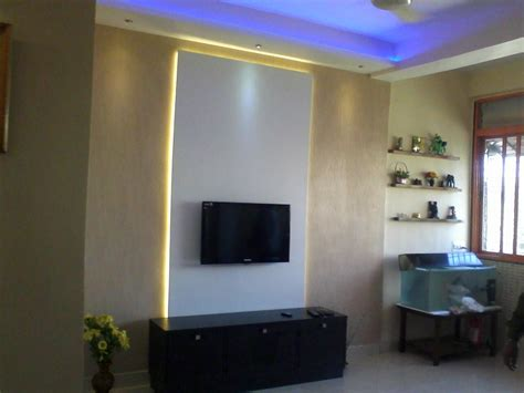 backlit tv panel with white laminates backlit glow with yellow lights and surrounded by wall