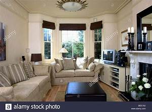 beige sofas in cream living room with black blinds on bay With cream and black living room furniture