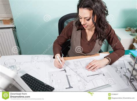 Woman Architect At Her Table Working On Blueprints Stock