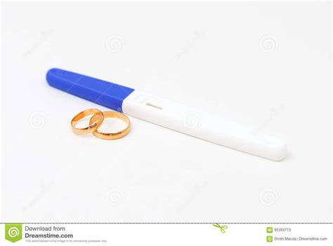 plastic pregnancy test and two wedding rings stock 95393773