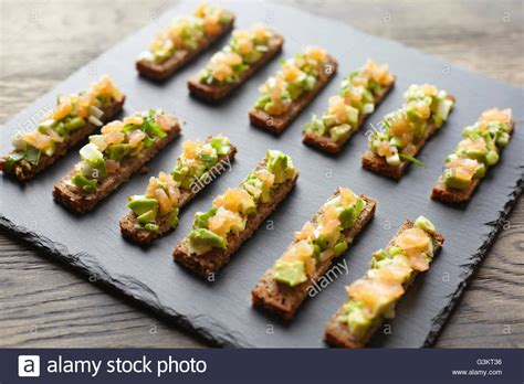 toast canapes guacamole smoked salmon and rye bread canapes stock photo