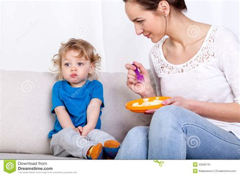 Mother Feeding Child On Couch Stock Photo Image 43206731