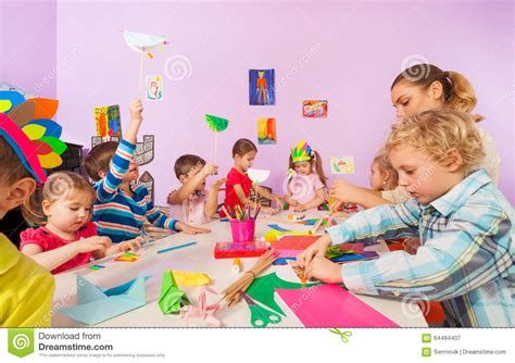 creative preschool children with stock image 514 | creative preschool children teacher group kids boys girls sit table glue paper draw images cut 64494407