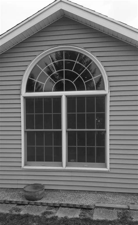 vinyl arch top window replacement brightens  bedroom