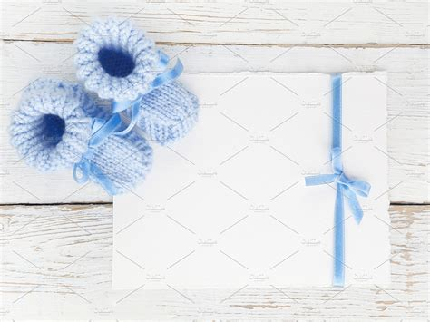 baby boy booties   blank card   white wooden