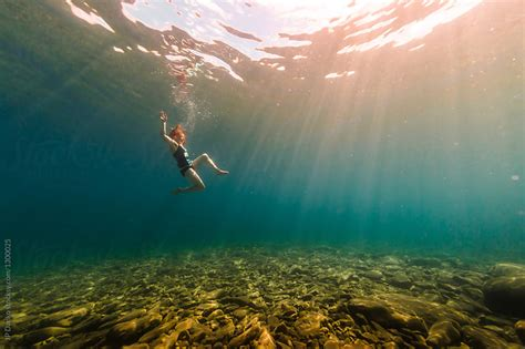woman swimming underwater  crystal clear summer lake