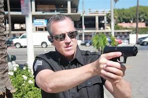 policeman hold suspect at gunpoint