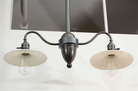 antique arm light fixture with milk glass shades at